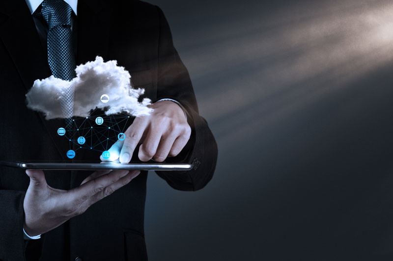 man holding computer and phone connected with cloud